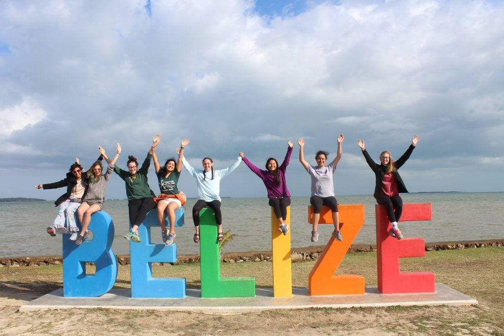 All eight student volunteers stop to pose with the Belize sign on the way to the airport on the last day.