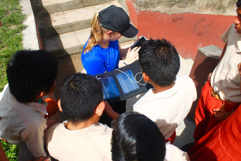 At Faith Nazarene School in San Ignacio, Meredith Glover '20 shows schoolchildren a solar powered phone charger to teach about the solar power system we were currently installing on their school's roof.