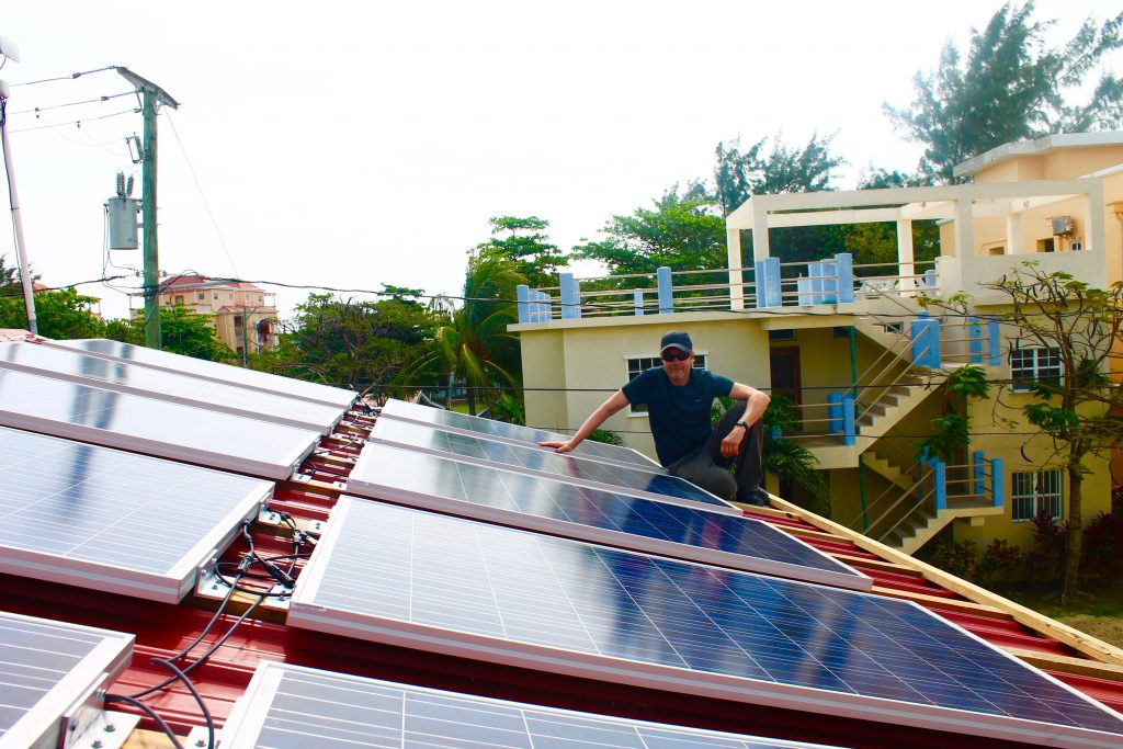 Professor James Skon with the ten-panel system installed at Ambergris Caye Elementary School in San Pedro, Belize.