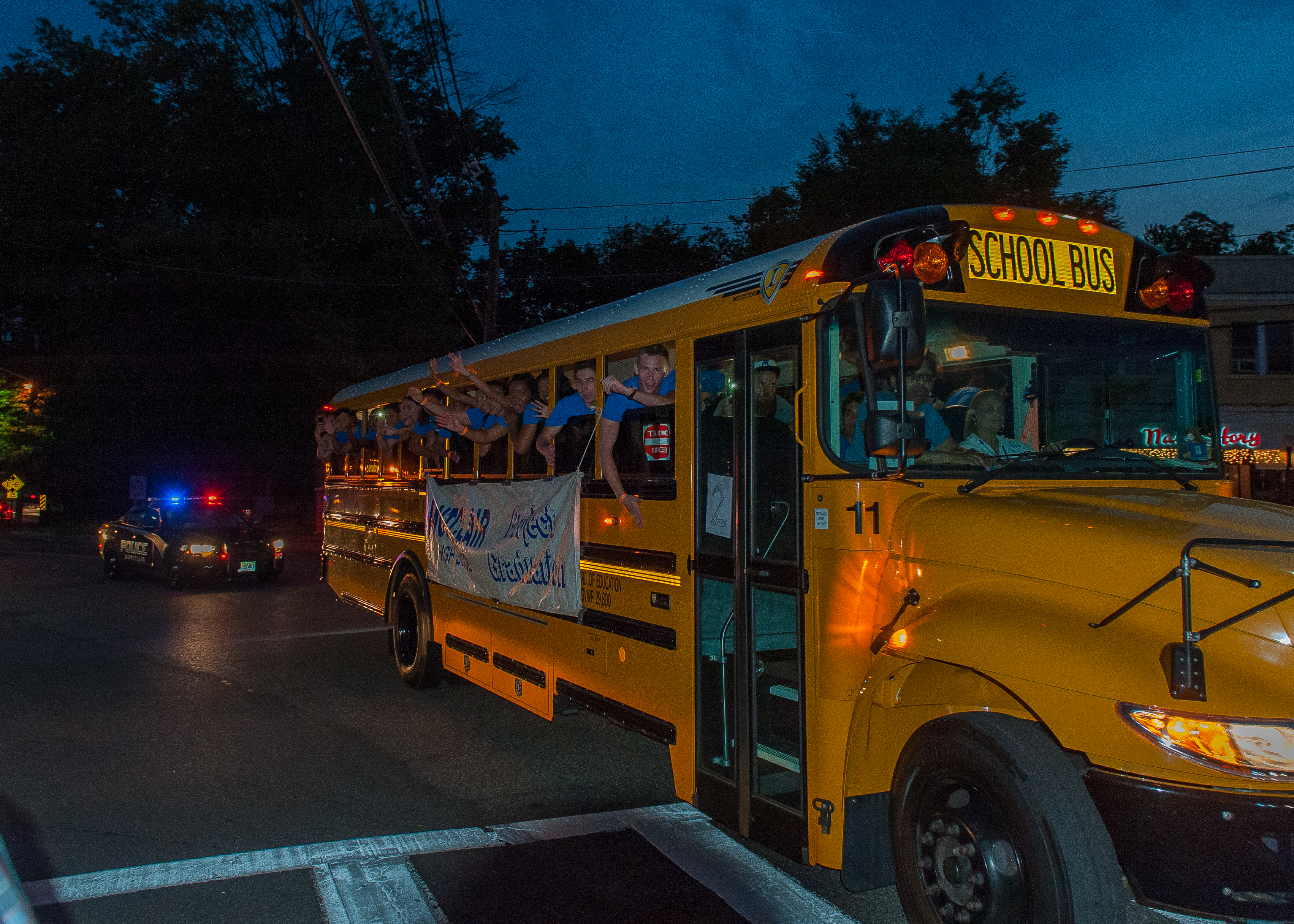 Students riding school busses through Watchung Plaza on their way to Project Graduation. Photo by Scott Kennedy for The Montclair Dispatch.