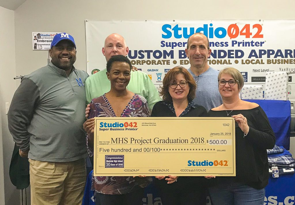 The 2018 MHS Project Graduation committee accepts a donation from Studio042